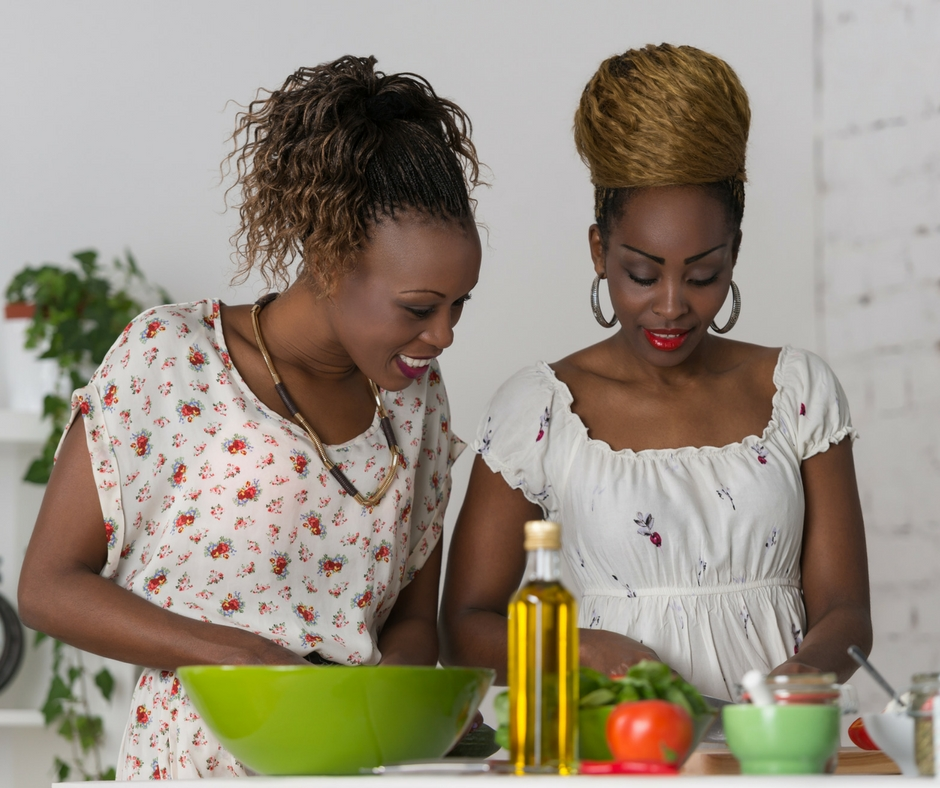 Two dark skinned women cooking together