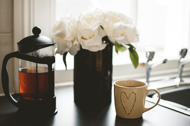 A pot of coffee, mug and vase of flowers
